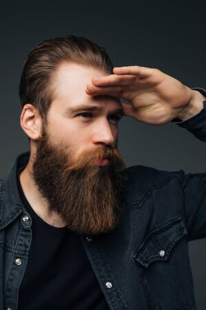 Young hipster man with long perfect beard looking far away on gray background Foto de archivo