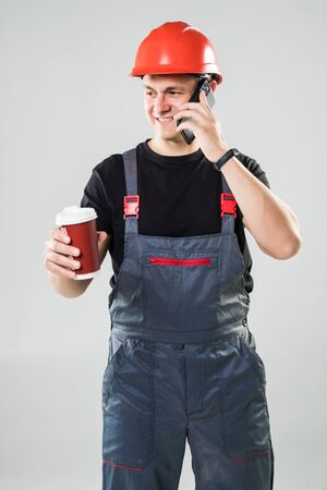Smiling worker in helmet drinking coffee to go talking on the phone isolated on white background