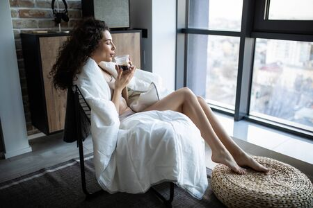 Beautiful woman in underwear sitting next to a window and enjoying a cup of coffee in the morning