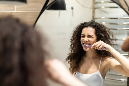 Portrait of attractive woman brushing teeth in bathroom and looking in the mirror at reflection. Banque d'images