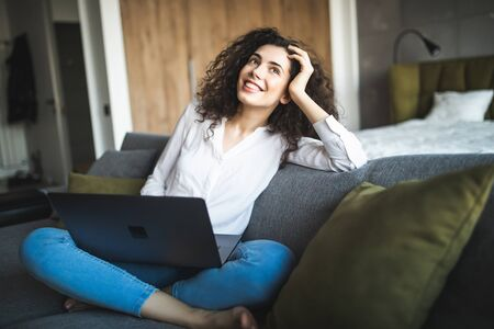 Smiling woman sitting with laptop on sofa in lounge