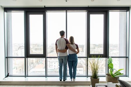 Young couple embracing standing near window and enjoying view from new apartment