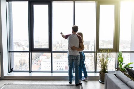 Back view of beautiful young business couple hugging while looking out the window 版權商用圖片