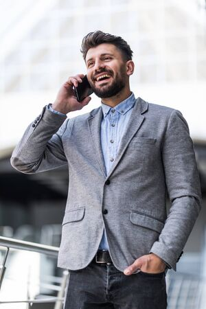 Portrait of a businessman having mobile phone conversation while resting after meeting . Businessman talking on cell telephone while standing in modern space indoors