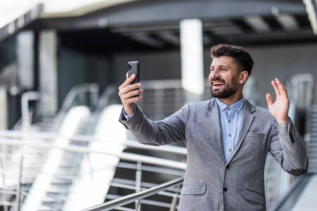 Young business man calling video call by mobile phone in office