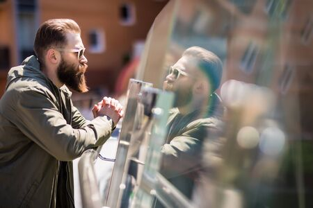 Handsome bearded man in sunglasses is looking at camera while standing on balcony