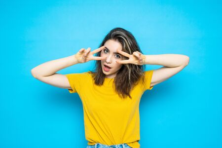 Image of cute young lady standing isolated over blue background. Looking camera showing peace gesture.