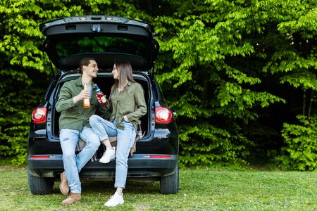 happy young couple sitting together in car trunk and drinking beer in forest outdoors