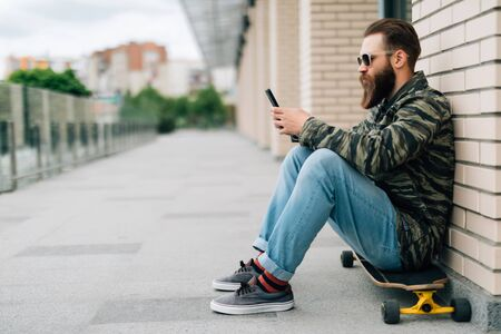 Young man using a cellphone while sitting at the skatepark.