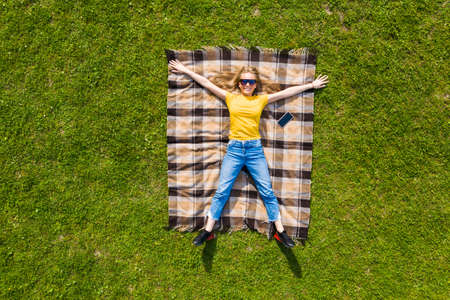Aerial view. Young girl lying and resting on lawn on sunny day in park on grass. Above view.