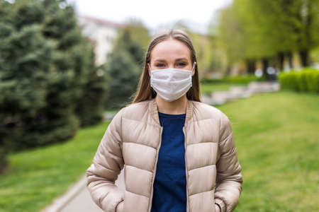 Woman wearing medical protective mask outdoors. Health protection during flu virus outbreak, coronavirus epidemic infectious diseases and air pollution in the city Banco de Imagens
