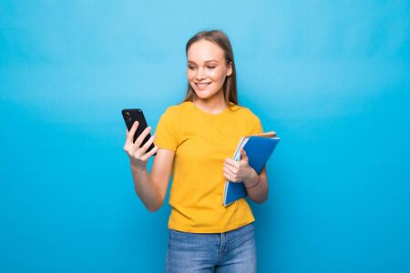 Excited young brunette woman standing isolated over blue background, using mobile phone while holding textbooks, looking away