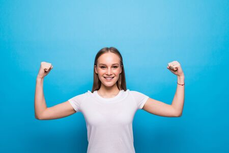 Portrait of woman raising hands to show biceps, feeling strength and confidence to achieve success isolated on blue background
