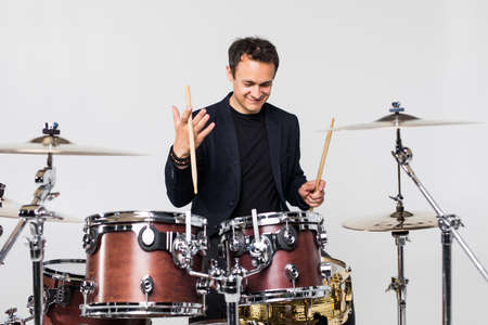 Young handsome man play with drumsticks sitting at drums isolated on white background