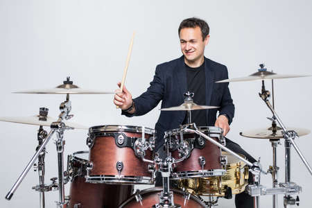 Young attractive man drummer playing drums and cymbals studio shot Banco de Imagens