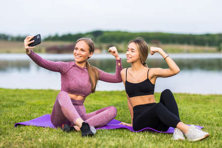 Beautiful girls taking a selfie with a smart phone before going for a run outdoors Standard-Bild