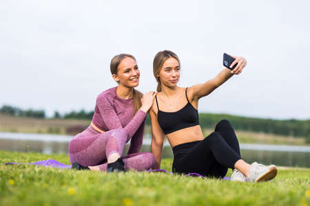 Beautiful girls taking a selfie with a smart phone before going for a run outdoors Banco de Imagens
