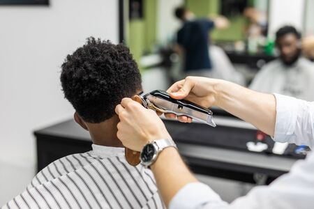 Barber trim hair with clipper on young unshaven black man in barbershop studio. Professional hairdresser cut hair with electric shearer machine on African guy.