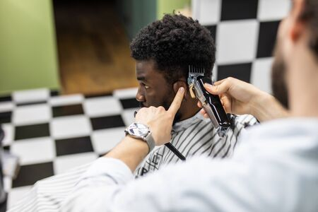 Closeup of process of trimming of hair in barber shop. Qualified barber keeping clipper in hands and correcting shape of hair to male client sitting on chair. 写真素材 - 150469058