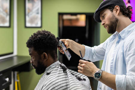 Closeup of process of trimming of hair in barber shop. Qualified barber keeping clipper in hands and correcting shape of hair to male client sitting on chair. Banco de Imagens