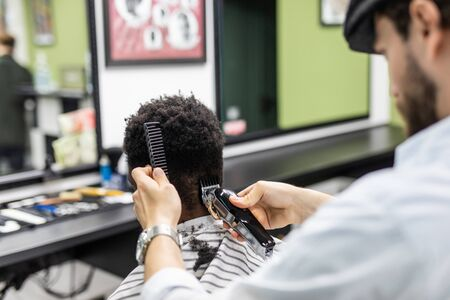 Portrait of young black man in barbershop.Handsome African guy makes new haircut in barber shop salon.