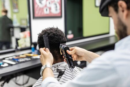 Closeup of process of trimming of hair in barber shop. Qualified barber keeping clipper in hands and correcting shape of hair to male client sitting on chair. 写真素材