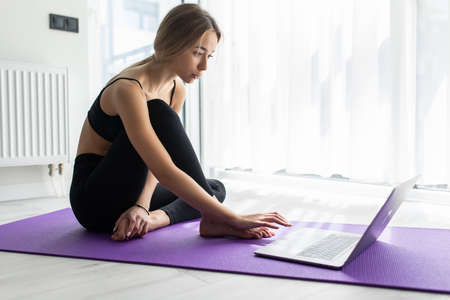 Glad, smiling and young woman lying on floor at fitness mat and using laptop computer resting after training Banco de Imagens