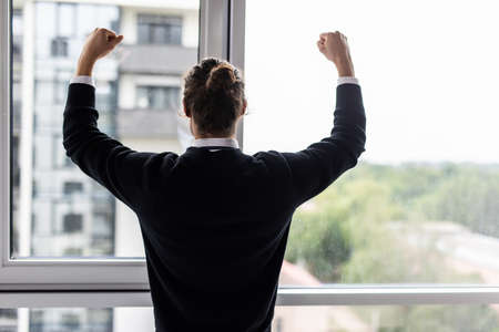 Incredible joy of winner businessman with raised hands near office window 免版税图像