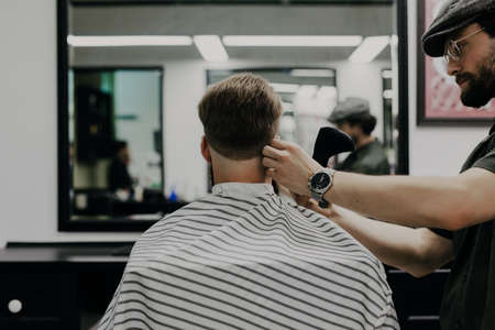 Haircut men Barbershop. Men's Hairdresser barbers. Barber cuts the client machine for haircuts.