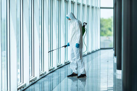 Coronavirus Pandemic. A disinfector in a protective suit and mask sprays disinfectants in the office. Protection agsinst COVID-19 disease. Prevention of spreding pneumonia virus with surfaces.