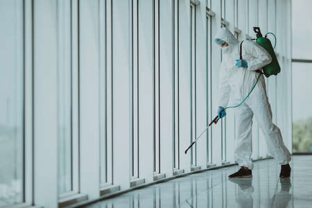 Professional fully armed disinfector against Covid-19 using sprays to remove bacteria from the surface at the hotel. Man wearing a protective mask, gloves and suit. Stock Photo