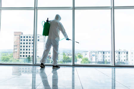 Professional fully armed disinfector against Covid-19 using sprays to remove bacteria from the surface at the hotel. Man wearing a protective mask, gloves and suit.