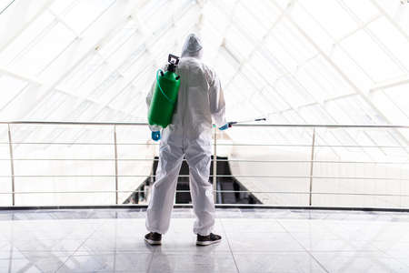 Professional fully armed disinfector against Covid-19 using sprays to remove bacteria from the surface at the hotel. Man wearing a protective mask, gloves and suit. Banco de Imagens