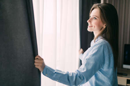Young girl opens the curtains and relaxing in the morning Stock Photo