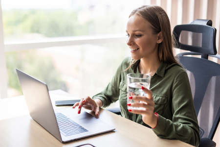 Happy entrepreneur working on line with a laptop and drinking water at office