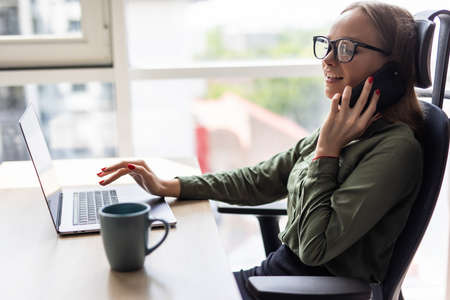 Young beautiful woman in glasses talking on mobile phone and using laptop with smile while sitting at her working place Banco de Imagens