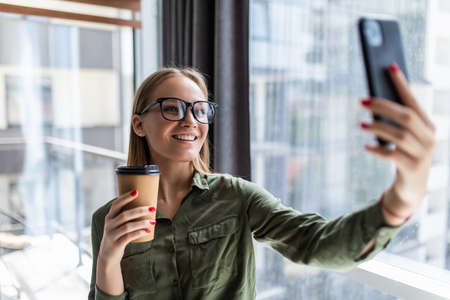 Photo of woman in formal wear standing holding takeaway coffee in hand and taking selfie on mobile phone in office Banco de Imagens