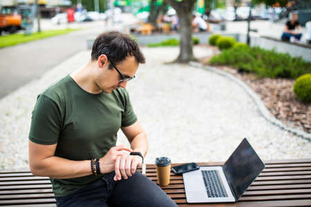 Stylish man sitting on bench with laptop and looking at watches.