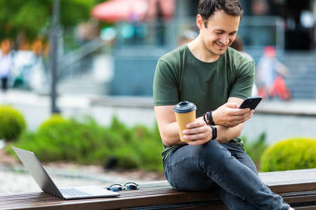 Cheerful young casual man using mobile phone while sitting at the city park, drinking coffee