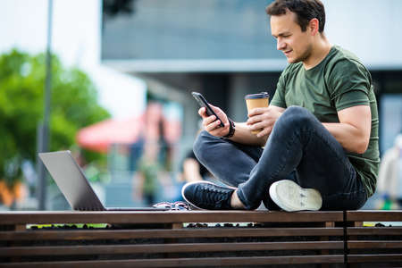 Young man sitting on the street bench using smart phone