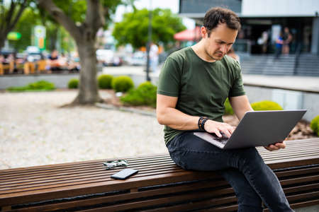 Handsome young businessman siting on a bench with his laptop on a street next to a park. Smiling businessman sitting on the bench and watching on the laptop in city park outdoors.