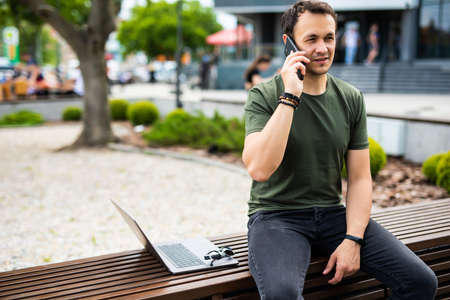 Handsome smiling young man sitting on a bench and talking on phone
