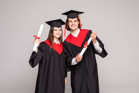 Young couple posing with their diplomas isolated on white background
