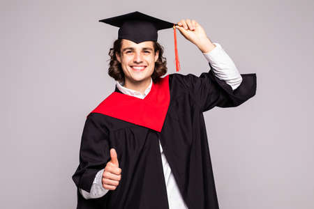 male graduation portrait smiling and standing over a white background