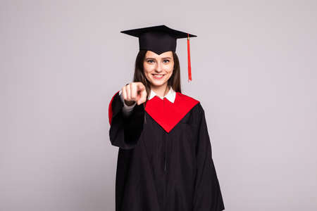 Female graduate student pointing with fingers on you on white background
