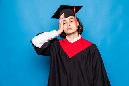 Graduate male student wearing black mantle and mortarboard in blue shirt holding his blue diploma. Place for advertising