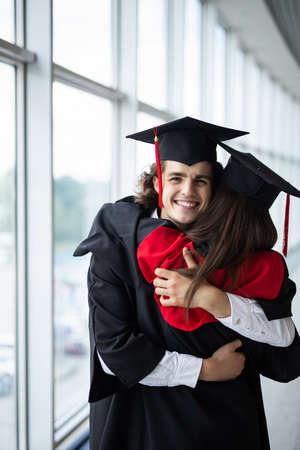 一个毕业生拥抱和享受的斗篷。美丽的毕业生女孩和男孩享受着毕业典礼。