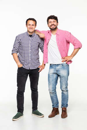 Two handsome men wearing casual t-shirt and jeans smiling and posing together on camera over white background
