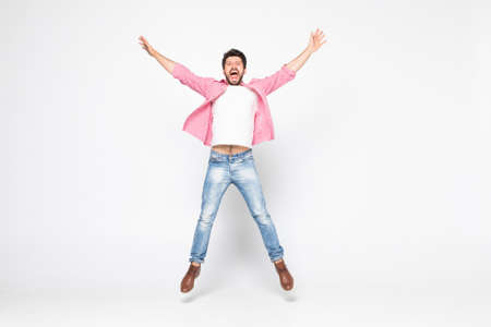 Excited young man jumping and smiling isolated