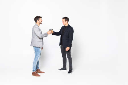 Young two men corporate executives standing and talking with coffee on white background.